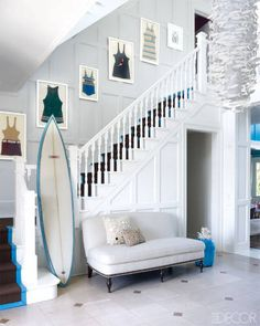 Framed vintage swimsuits line the staircase in the entry; the custom light fixture is by Scabetti