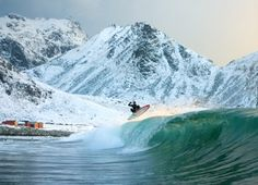 Professional surfer Cheyne Cottrell performs an aerial maneuver above Norway's Arctic Circle on a beach in the remote Lofoten Islands at approximately 11pm.  Via National Geographic  Photograph by Yassine Ouhilal Cold water surfing, winter surf, surf en eau froide