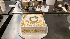 A square cake with a gold and silver color scheme, fondant stars on wire and a hand illustrated diamond ring.
