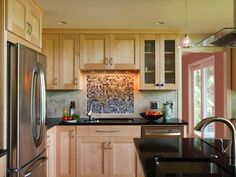 A multicolored mosaic tile backsplash adds depth and visual pizazz to this neutral contemporary kitchen. Stainless steel appliances serve as a crisp counterpoint to the pale wood cabinets.