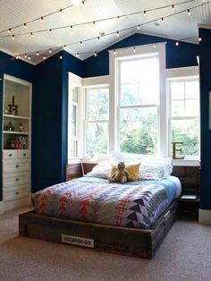 Love this bedroom! I especially love the navy blue walls and how the very white window frames give it a brighter look! Not to mention the string lights are adorable!