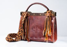 Inspired on the Wayuu Tribe in the Colombian Guajira, this tribal bag evokes through its colors and artistic technique an important feature of this clan, women as host and organizer of the very active and independent community. Handmade, hand-stained and hand-stitched leather satchel. Exterior features a vintage-style frame construction with antique brass-tone hardware with snap-lock closure for a timeless touch. Colorful handcrafted crochet shoulder drop inspired by the Wayuu Tribes from…