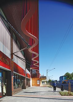 Oblique view along the main street facade, with the kinetic edge of the red curtain brise-soleil above.