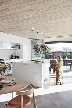 Henry and Thea in the integrated kitchen by Top Knot Carpentry & Joinery. The island and splashback are in Smartstone 'Carrara', while 'Absolut Blanc' features on the rear bench. Oven, cooktop, rangehood, combi oven, dishwasher and coffee machine, all Smeg. | Photography: Maree Homer, Nic Gossage