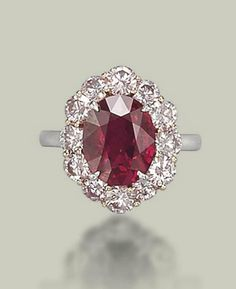 AN EXCEPTIONAL RUBY AND COLOURED DIAMOND RING  Set with an oval-shaped ruby, weighing approximately 5.09 carats, to the pink diamond surround, mounted in platinum and gold #rubyring