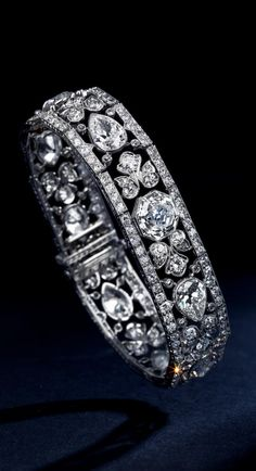 An Exquisite Edwardian diamond bracelet, circa 1910. Of floral motif, centring an octagonal-shaped diamond, weighing approximately 3.75 carats, to a line of pear-shaped diamonds, within a millegrain openwork frame; estimated remaining diamond weight: 18.00 carats; mounted in platinum.