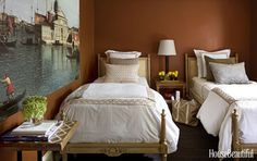 A Canadian townhouse's guest bedroom, which is equipped with a pair of 18th-century beds upholstered in a Pierre Frey fabric, exudes warmth with walls painted in Benjamin Moore's Terra Mauve.Click through for more colorful bedroom decorating ideas.