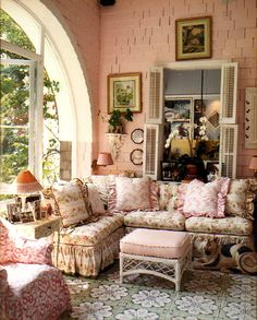 I loooove this room! I love the sofa and want it!  Looks like this may have been a patio that was enclosed to be used as a sunroom....all in all a beautiful space..color, rug, furniture.