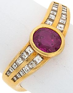 The ring features an oval-cut ruby measuring approximately 6.40 x 5.00 x 3.50 mm and weighing approximately 0.90 carat, enhanced by square-cut diamonds weighing a total of approximately 0.45 carats, set in 18k gold. Gross weight 5.40 grams.
