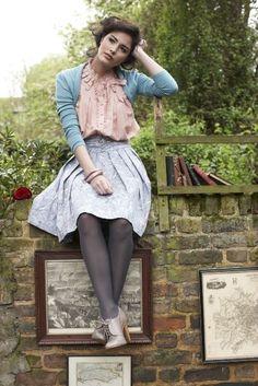 All pastels. Lavender midi skirt, pink blouse, blue cardigan, grey tights, tan heeled oxfords.