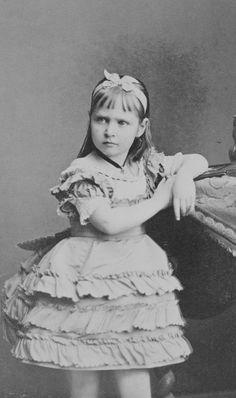 Princesa Alix de Hesse em pé com o braço esquerdo repousado sobre uma mesa. Em 1877.
