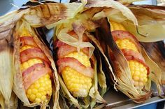 INGREDIENTS:8 ears corn on  cob1 lb. sliced baconMETHOD:Gently pull back thusk exposing corn. Do not remove husk. Remove corn silk and use brush to make sure all the silk is removed.Take strip of bacon  wrap it around corn. Fold corn leaves back over, covering bacon  corn. Tie leaves w/ butcher string  repeat  process for each ear. Place ears on hot grill  cook, turning occas until bacon is cooked and corn is tender, approx 15-20 min.