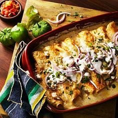 """These decadent enchiladas are named """"Swiss"""" because of all the cream and cheese they contain. The recipe isgenerally credited to a Mexico City coffee shop called Sanborns. This version is from Silvana Salcido Esparza, chef-owner of Barrio Café and Barrio Queen in Tucson."""