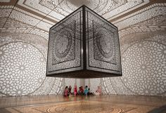 VOTRE ART----Winner of both the public and juried vote of Artprize 2014, Pakistani artist Anila Quayyum Agha exercises the architecture of the Grand Rapids Art Museum in Michigan by infilling it with a dynamic interplay of shadow and light. Intersections comprises a 6.5 foot laser-cut wooden cube pierced with carefully crafted patterns and illuminated from the inside, which casts expansive, lace-like geometries onto the surrounding walls, ceiling and floor.