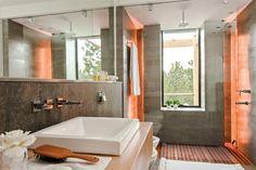 Deco moderna: dos casas con estilo actual En el baño en suite preponderan las líneas simples y se repite la combinación gris/madera, fiel a los tonos del hogar..