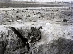 """WW1: One of France's colonial troops is KIA sitting upright in what looks like a bomb crater on the Western Front, undated. During WW1 the French Army conscripted some 440,000 colonial troops from Africa and French Indochina. An estimated 40,000 of these troops gave their lives for """"their"""" country."""