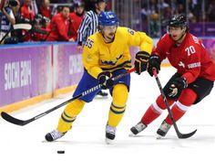 DAY 8:  Erik Karlsson #65 of Sweden and Denis Hollenstein #70 of Switzerland compete during the Ice Hockey Men's Preliminary Round Group C - Sweden vs. Switzerland