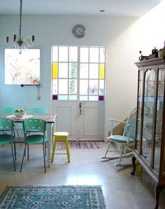 Sillas de color, lámpara de techo tipo araña, puerta con vidrio repartido, silla mecedora.: