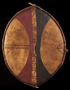 A twentieth-century Masai warrior's buffalo-hide shield from east Africa; the painted symbols/sirata identify the holder's age, clan and battle feats.