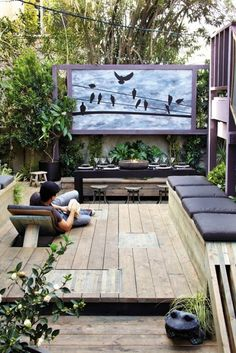 Gorgeous outdoor living area, complete with seating, an eating area, greenery and art. Lovely! /ES