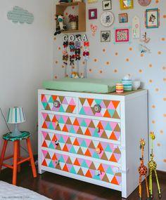 Duas ideias bacanas nessa foto: parede e cômoda decoradas com  com adesivo em diferentes cores e formato.