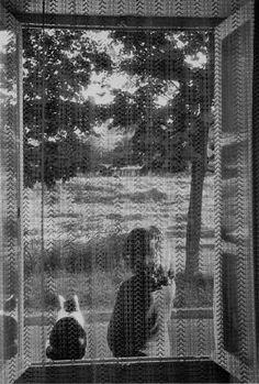 Through a veil: cat and girl. France. 1978. Photographer: Edouard Boubat