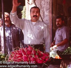 This travel photograph depicts a man waving while tending to a food stand. The food stand displays bright red radishes. Image captured in Syria. See also: Middle Eastern FoodMarkets &nbsp...