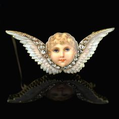 Beautiful Victorian brooch designed as the face of a cherub in polychrome enamel inbetween a pair of wings with diamond highlights English circa 1885