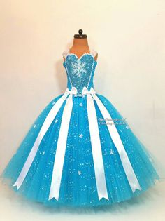 This beautiful handmade extremely super sparkly Elsa inspired dress is made with over one hundred metres of sparkly material to make a dress fit for a queen. The dress and cape have a showering of white snowflakes and a large one at the front of the top to make the dress stand out