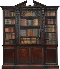 A George II mahogany breakfront bookcase circa 1740, possibly to a design by William Kent, originally an alcove fitment with consequential alterations to the sides the fluted cornice with broken triangular pediment above three doors, the centre one with an oval mullion and fluted carved pilasters, headed by corbels, the lower part with a scroll moulding above divided doors, flanked by two banks of four drawers,