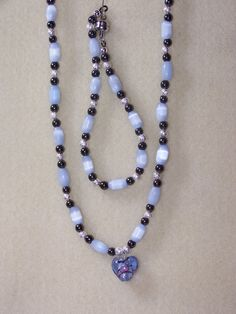 Blue glass heart charm necklace and bracelet with blue oblong tigers eye, trimmed with black hematite beads and silver spacers.