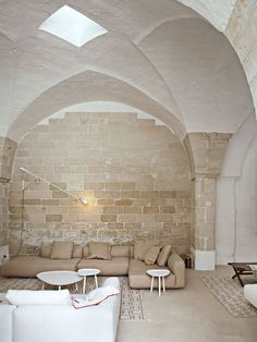 Former Oil Mill is a minimal residence located in Puglia, Italy, designed by Palomba Serafini Associati. The building was originally constructed in the 1600s, and recently restructured into a residential building. The architects focused on maintaining as much of the originally structure as possible. The interior is characterized by wide communal spaces framed by columns with sloping ceilings. Skylights illuminate the space from above, providing abundant natural lighting.