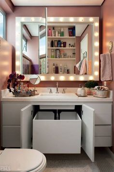 Reforma deixou o banheiro com luzes de camarim, paredes cor-de-rosa e marcenaria inteligente.