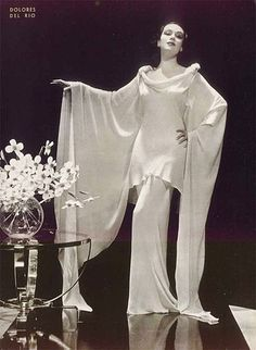 Argentinian actress Delores Del Rio, 1935. Gorgeous bias cut gown, scooped necklines  and sweeping sleeves. By CINEGRAF magazine [Public domain or Public domain], via Wikimedia Commons