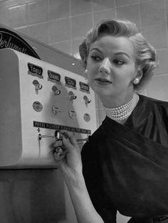 Woman Operating Coin-Operated Perfume Vending Machine Premium fotoprint van Nina Leen - bij AllPosters.be