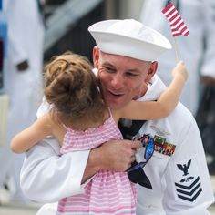 A sailor from USS George Washington is reunited with his daughter at the pier of the aircraft carrier, at Fleet Activities Yokosuka, Japan, August 8 2014.