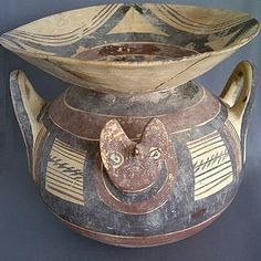An ancient Daunia funnel krater. From the Apulia region of Italy. Dates to circa the 4th Century B.C. Large globular body with a funnel-shaped mouth and stylized animal heads on the shoulders between the vertical handles. Has a rich red, black and brown paint, with geometric ornaments on a creamy white ground. Intact said for repair on rim. Measures 10inches wide x 9inches high.