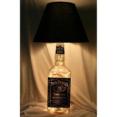 Add a fun touch to the decor of any home with a table lamp made from a recycled liquor bottle. This Jack Daniels lamp offers a black shade and white Christmas lights inside the bottle.