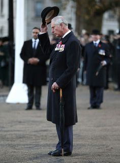 Prince Charles Photos Photos - Prince Charles, Prince of Wales doffs his hat to members of the Welsh Guard parading past, after he laid a wreath at the Guard's Memorial for the Welsh Guards' Regimental Remembrance Sunday on November 13, 2016 in London, England.  The Queen, senior politicians, including the British Prime Minister and representatives from the armed forces pay tribute to those who have suffered or died at war. - The Royal Family Lay Wreaths at the Cenotaph on Remembrance Sunday