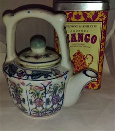 Chinese style single serve tea pot. Blue and white flora Asian style tea for one pot. It is stamped made in China on the bottom. The little pot has a blue flora design with pink accents and gold metallic paint. It measures 6 inches to the top of the handle. It is 3 inches high not counting the lid. It is 11 1/2 inches counting the base of the spout.  The little tea pot is perfect for a cup of tea for one person.