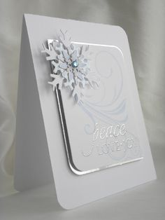 """BY Geri. Layered snowflake made with Spellbinders dies, and a Stampin' Up punch, held together with a snowflake brad with a gem on top. Sentiment, from Papertrey Ink, stamped in VersaMark and heat embossed with silver powder. Flourish from Papertrey Ink's """"Fancy Flourishes."""""""