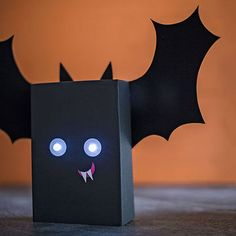 With eerie glowing eyes and goofy grin, this nocturnal critter will happily perch on a mantel or a protected front porch.                 To make, cut the top flaps off a box (we used a 16-ounce pasta box), then flip it over. Use a glue stick to cover the sides and bottom with black wrapping or construction paper. Halfway up the front, mark spots for eyes 2 inches apart. With a craft knife, cut an X for each eye (an adult's job), then widen each of the holes to measure 3/8 inch across…