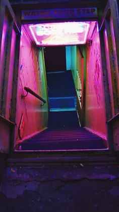 """image description: city stairwell leading down decorated with a """"watch your step"""" sign and pink, purple, red, and green neon lights Vaporwave, Cyberpunk, The Wicked The Divine, Neon Noir, Catty Noir, Neon Aesthetic, Violet Aesthetic, Aesthetic Japan, Nocturne"""