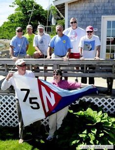 "2014-06-24 NYC Flag Raising, photographed Saturday by David Leaming during the Work Party. ""Art and Sandy Hall prepare to hoist the new Northport Yacht Club 75th anniversary flag in front of the clubhouse as members and officers watch during a work party on Saturday, June 21. Watching, from left to right, are John Lojek, John Lightner, Steve Fein, Jon Linn, Gordon Fuller and Jim Facey. Plenty of fun events are scheduled this summer for the anniversary."
