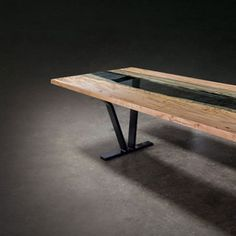 The colors and design of the SENTIENT Colorado modern dining table suggest the south west United States. The glass-filled gap between the edges of a live edge s