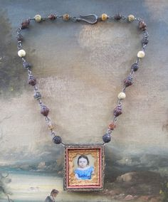 This listing is for a pair of necklaces. One is on a chain of sterling silver wire wrapped antique rosary beads. An antique locket that once held a tintype now holds a portrait of a beautiful young girl. This locket is exceptionally beautiful. Its made of carved wood, trimmed with gold paint and trimmed in velvet and brass. The rosary beads are all from France and have extra large holes. This required me to use exceptionally heavy sterling silver wire. The wire adds a fabulous texture to the…