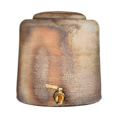 This water jug has been wood fired in for 9 days, using 15 cords of wood. No glazes were applied; the wood ash from pine and cotton wood and the glowing atmosphere of the kiln creates the color and finish. No two pieces are alike in this process. Made in an anagama in Tres Piedras, New Mexico along the Seco Creek by artist Logan Wannamaker for Wonder Valley. Brass spigot, wood fired ceramic lid included Holds roughly 3-4 gallons of water  Hand wash only