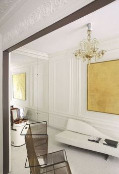 L'antichambre joue sur le blanc des murs et le lustre doré à la feuille d'or. Plus de photos sur Côté Maison http://petitlien.fr/836g