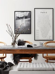 Scandinavian inspired dinning space with a wood dinning table and chairs, throws, and black and white art /