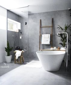 I love the concrete style walls and flooring in this bathroom. A lovely shower corner and huge stand alone bath with plenty of rustic touches.